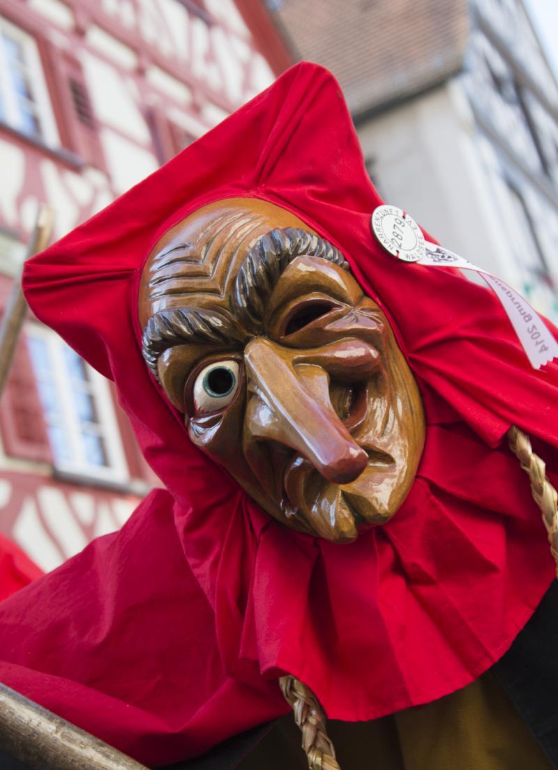 Das Schrättele mit seiner typischen Maske bei der Ein Mundwinkel nach oben und einer nach unten zeigt