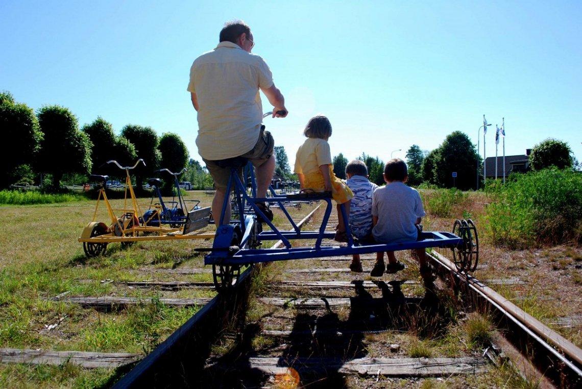 Vater mit drei Kindern auf Draisine