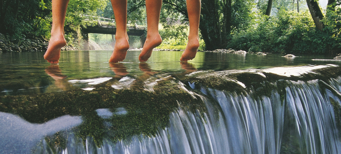 childrens feet hanging over a river in Austria