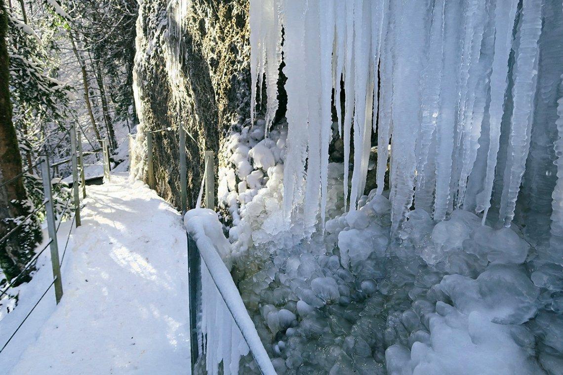 Verschneiter Weg und Eiszapfen am Eistobel im Winter