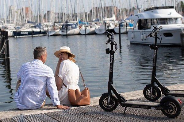 Paar mit Dethleffs E-Scooter im Hafen