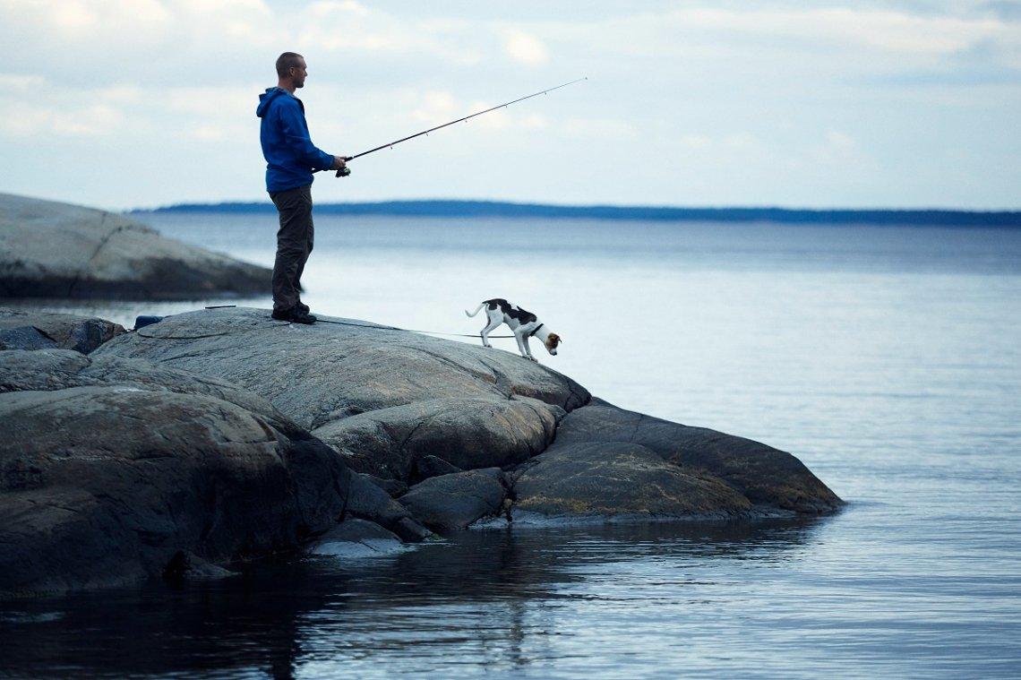 Angler mit Hund auf einer Schäreninsel in Schweden