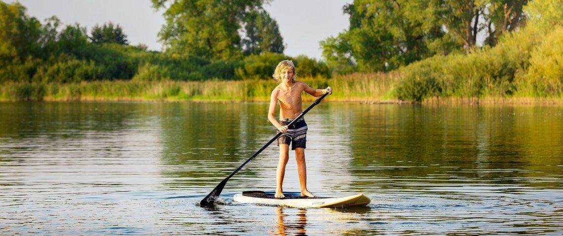 Junge beim Stand-up-Paddeln auf einem See in Mecklenburg