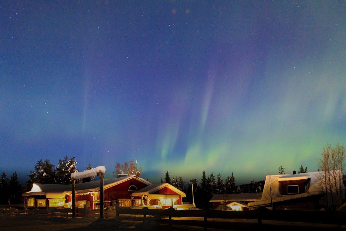 Polarlicht über beleuchtetem Hotel