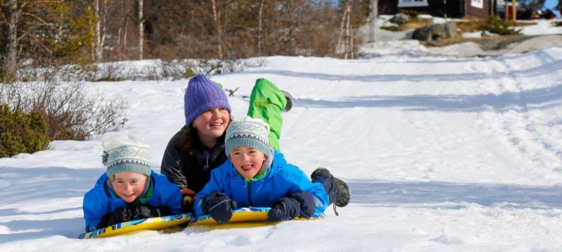 Kinder beim Rodeln im Schnee in Norwegen