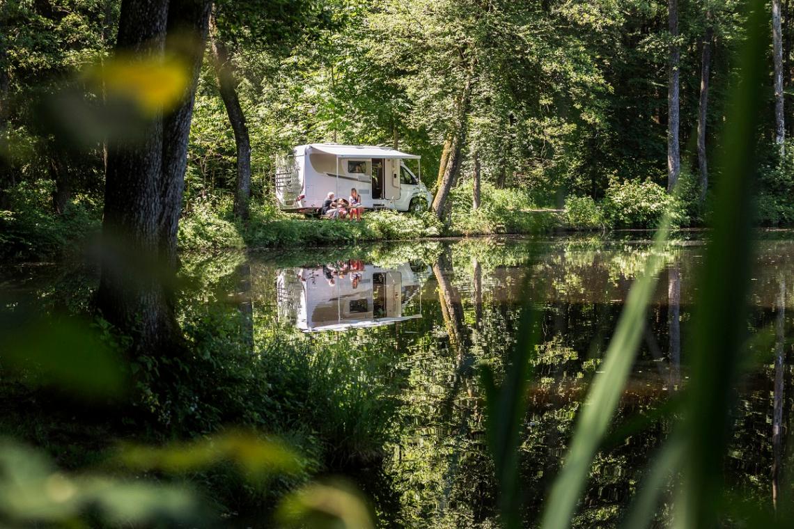 Carado Wohnmobil unter Bäumen am See