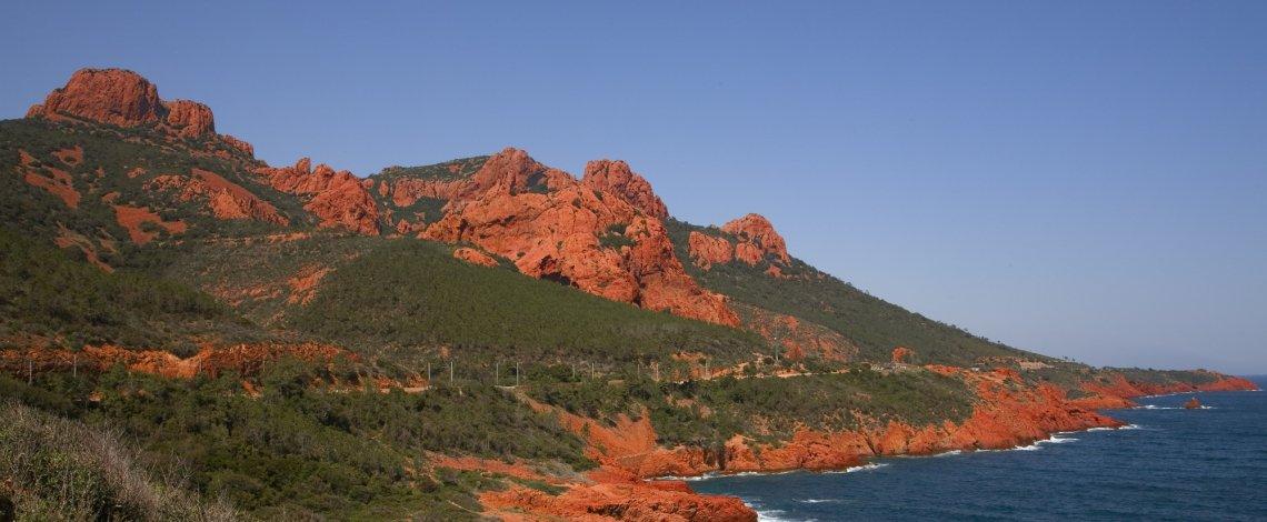Blick von der Küste auf die roten Felsen des Esterel Massivs