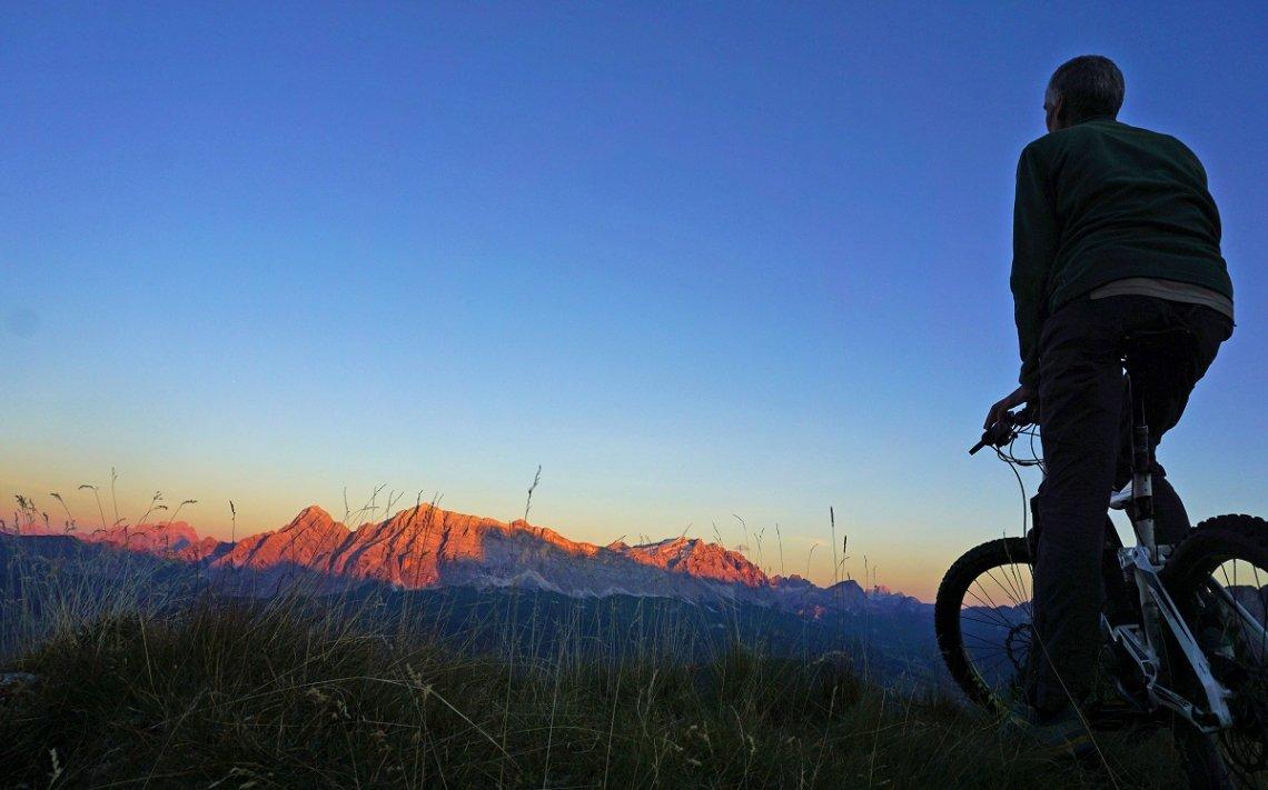 Radfahrer mit E-Mountainbike bei Sonnenuntergang in den Bergen