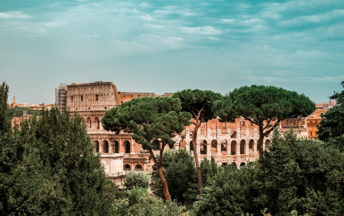 View through the trees onto the colosseum in Rome