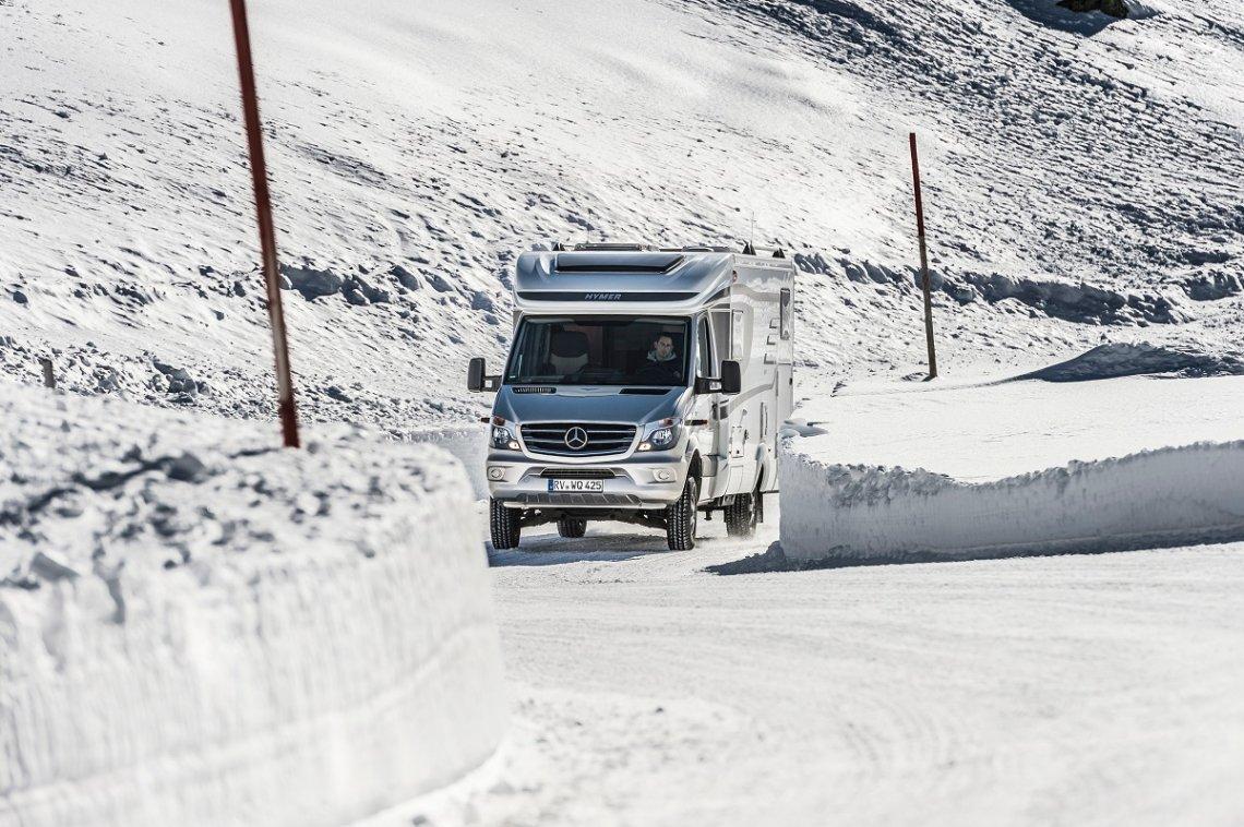 Hymer Reisemobil auf verschneiter Strasse in den Bergen
