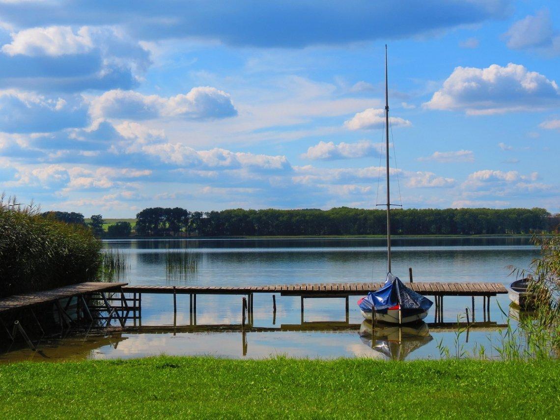 See in der Uckermark mit Segelboot am Steg