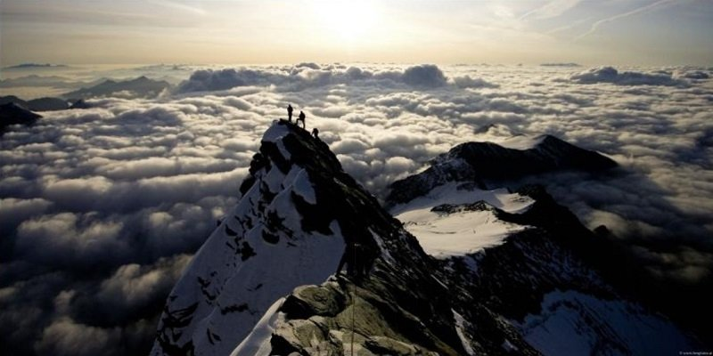 Hikers above the clouds on the summit of the Grossglockner