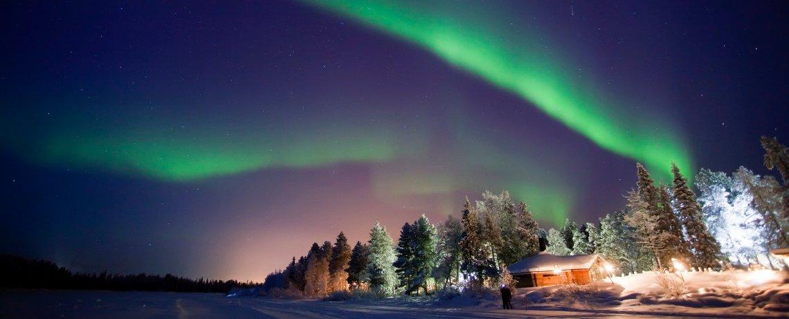 Nordlicht über Hütte im Wald