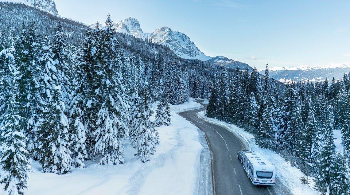 Een auto met caravan in de bergen