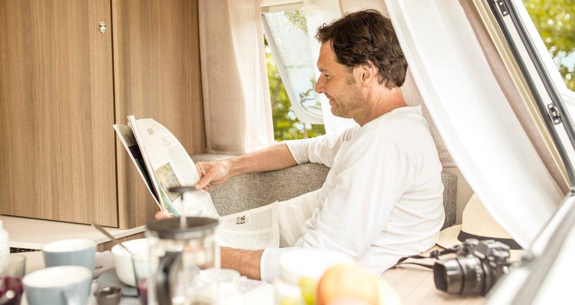 Comfortabel de krant lezen in de caravan