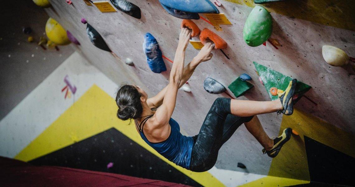 Frau beim Bouldern in der Boulderhalle