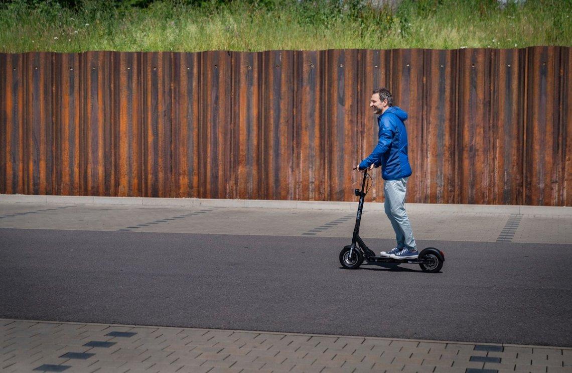 Mann fahrend mit einem Hymer E-Scooter