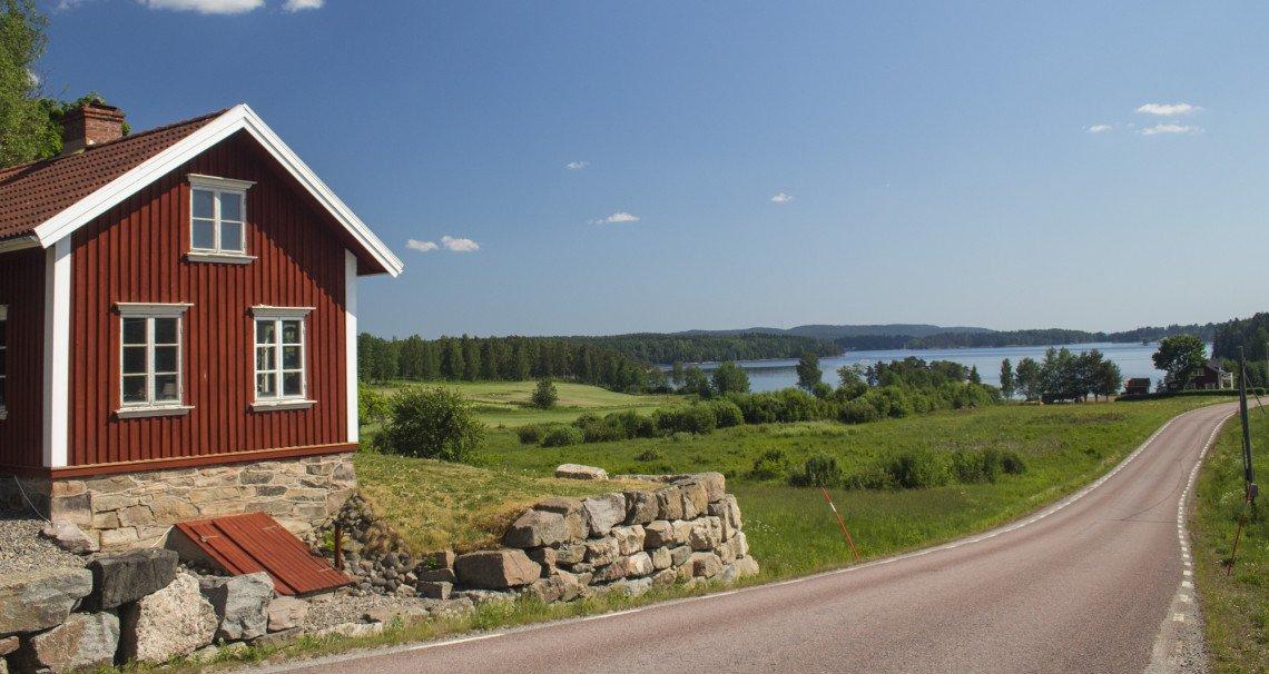 Sommeridylle in Schweden mit rotem Holzhaus, See und Wald
