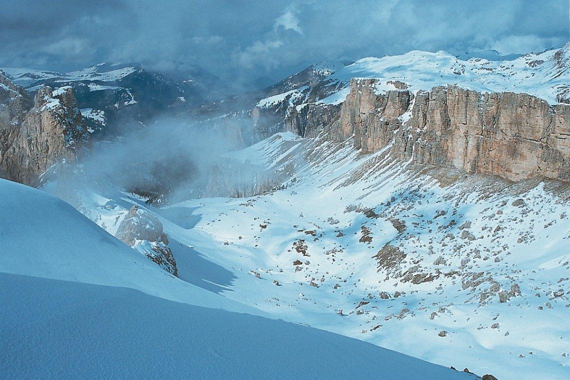 Skigelände zwischen mächtigen Felsflanken im einsamen Chedultal in den Dolomiten