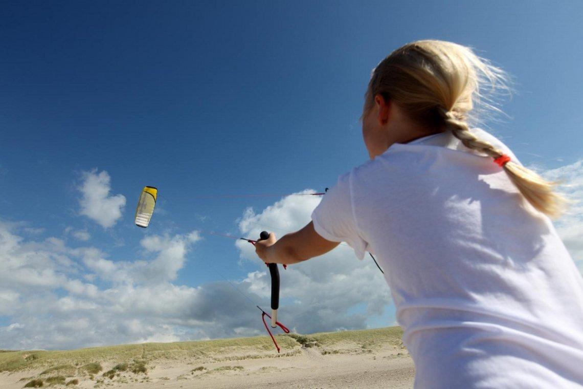 Mädchen beim Drachensteigen lassen am Strand